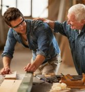 Picture of two carpenters at work. A young man is preparing a plank smiling towards an older man who is patting him on the back.