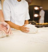 Team of bakers kneading dough in a commercial kitchen